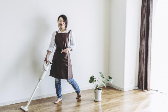 スティック掃除機で掃除をする女性
